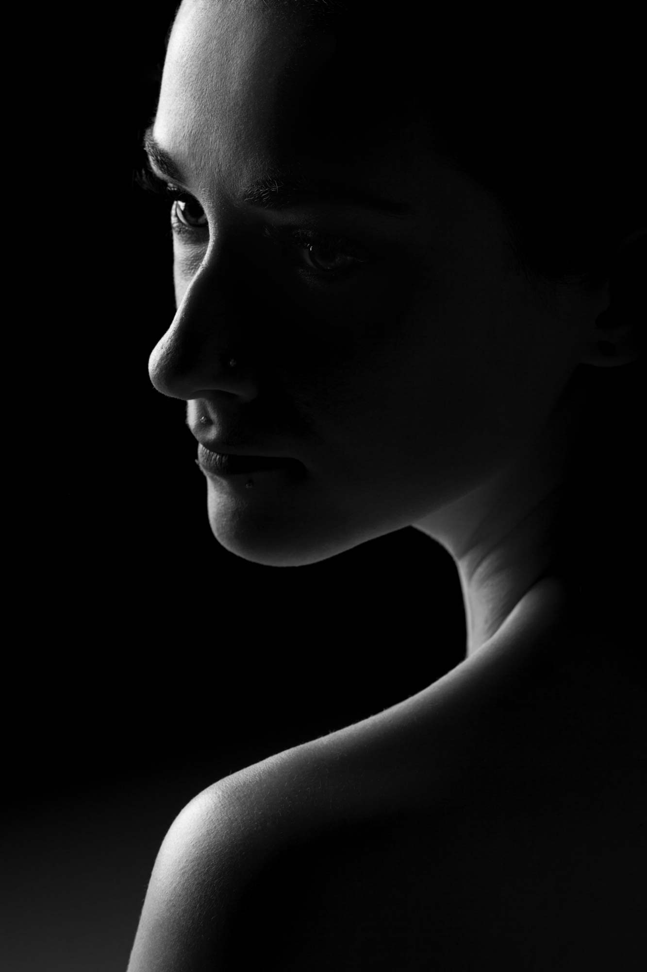 Dramatic black and white portrait of woman in studio shot in Boulder, Colorado