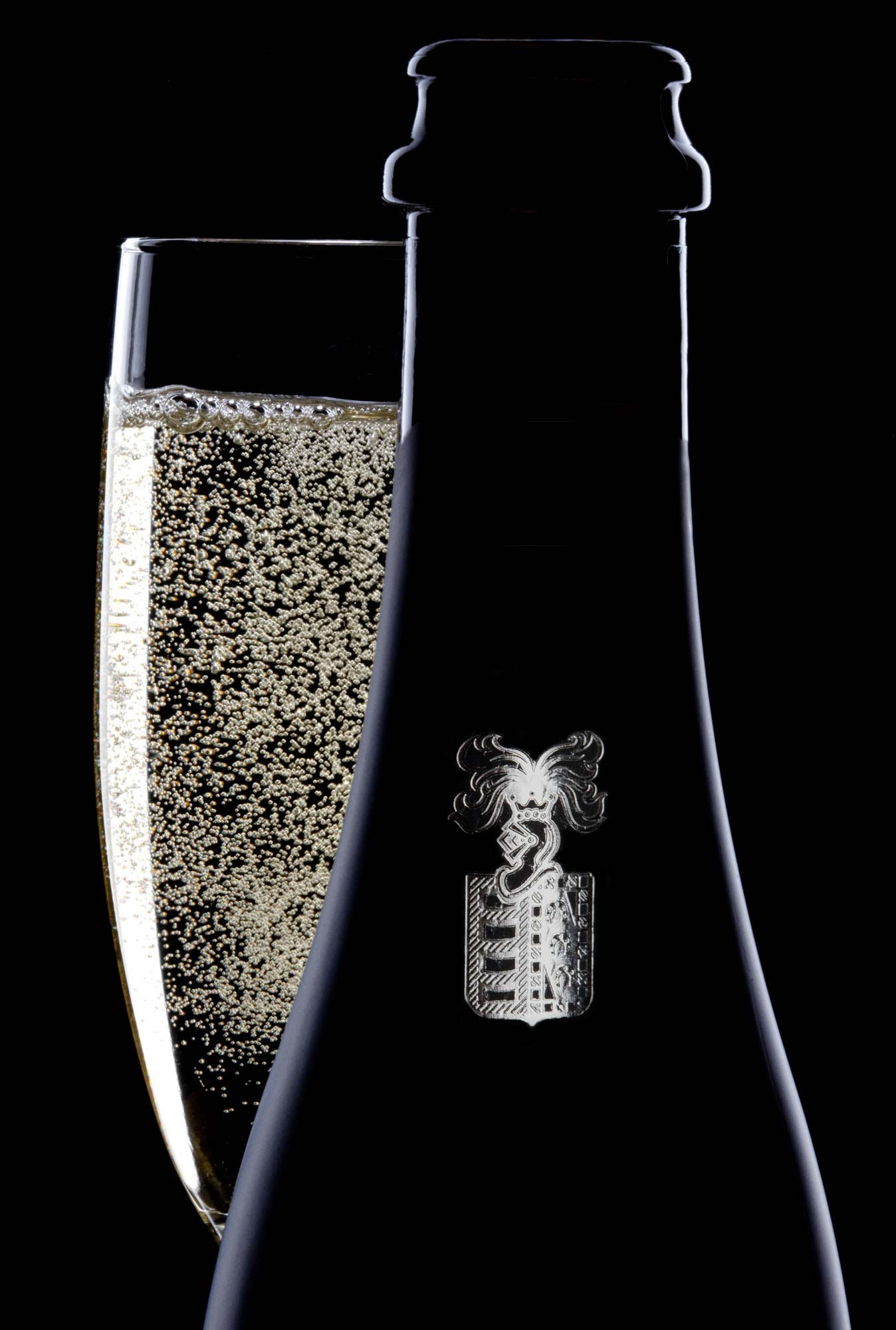 champagne bottle and glass on black. Dramatically lit product photography