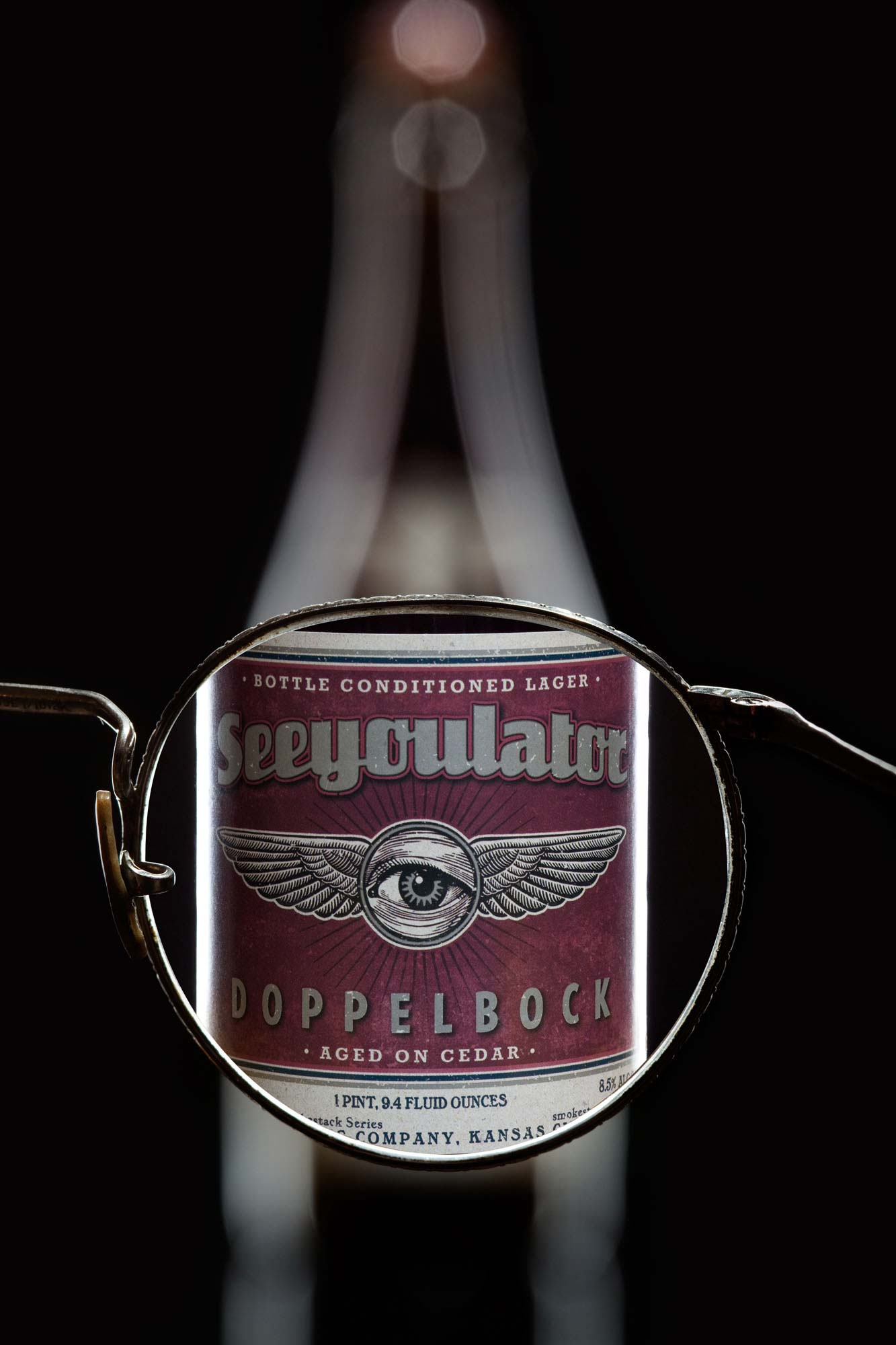 Looking through glasses lens making blurry beer bottle sharp - See You Later Doppelbock Cider | Bottle Photography | Dramatic Product Photography  | Still Life Photography | Shot in Denver, Colorado