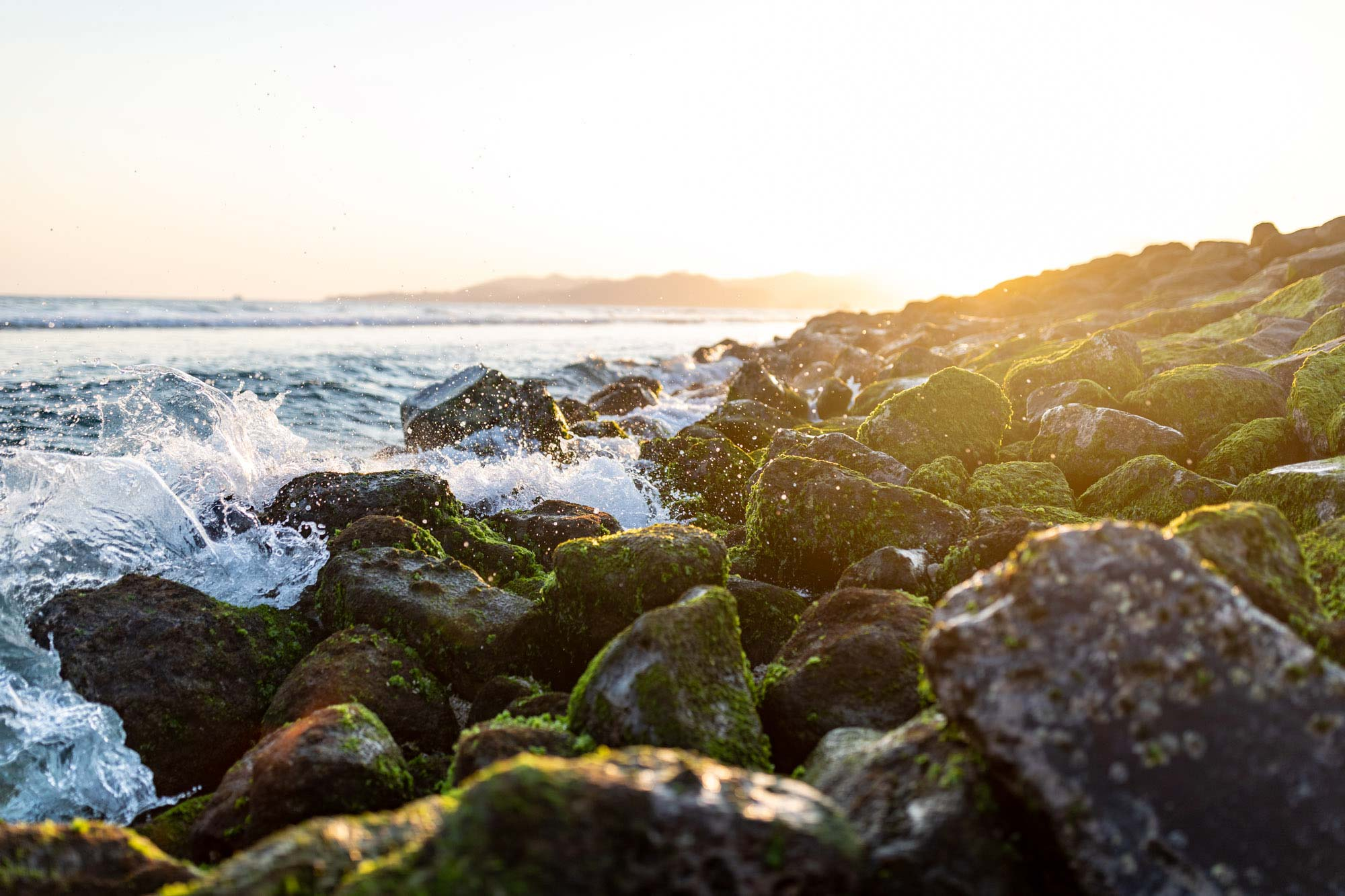 Water splashing on rocks at sunset in Candidasa, Bali, Indonesia. Lens Flare, Travel Photography