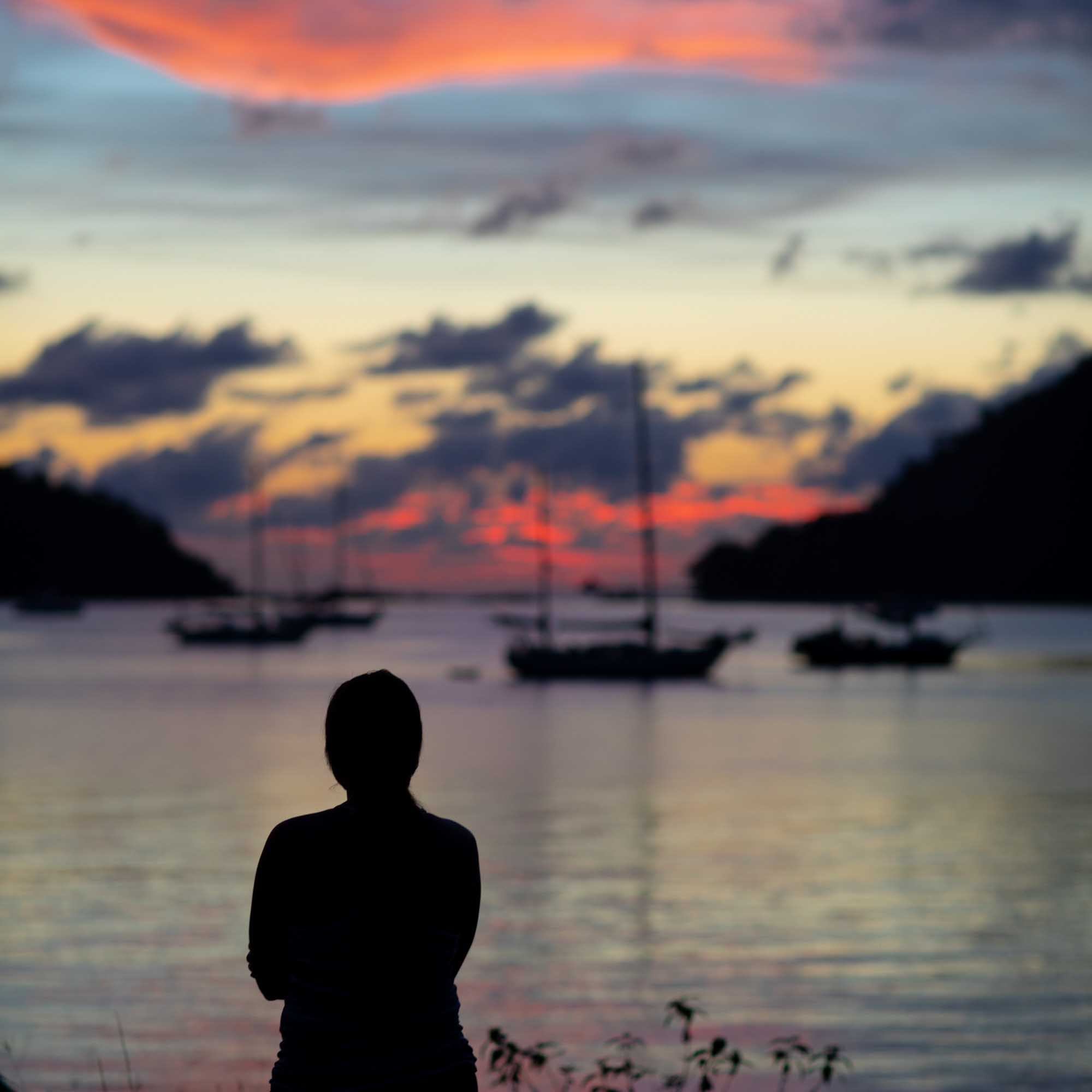 Silhouetted woman watching colorful sunset in Langkawi, Malaysia with boats in background | Travel Photography