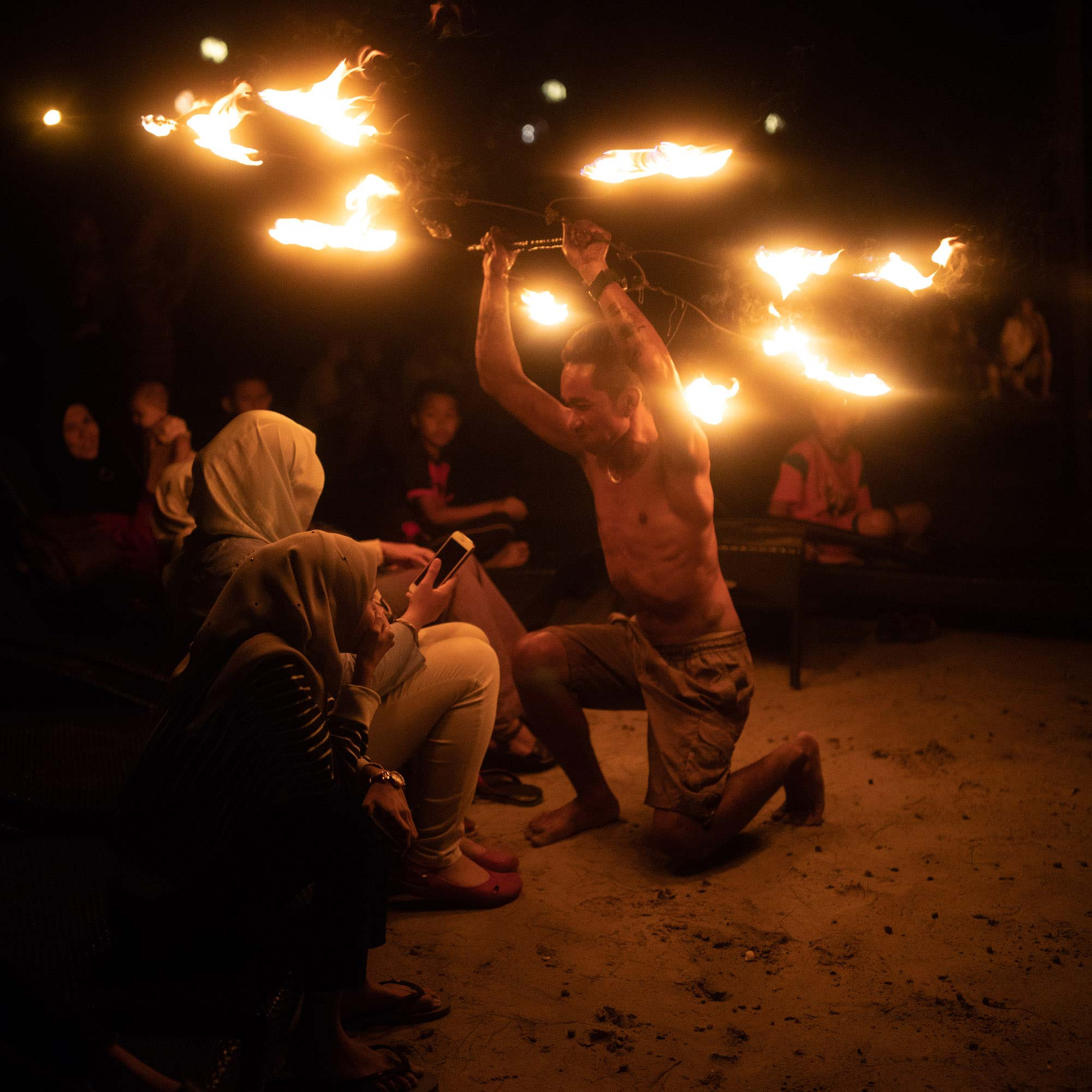 Man spinning fire in a circle in front of crowd | Travel Photography | Malaysia Sepang | Avani Resort