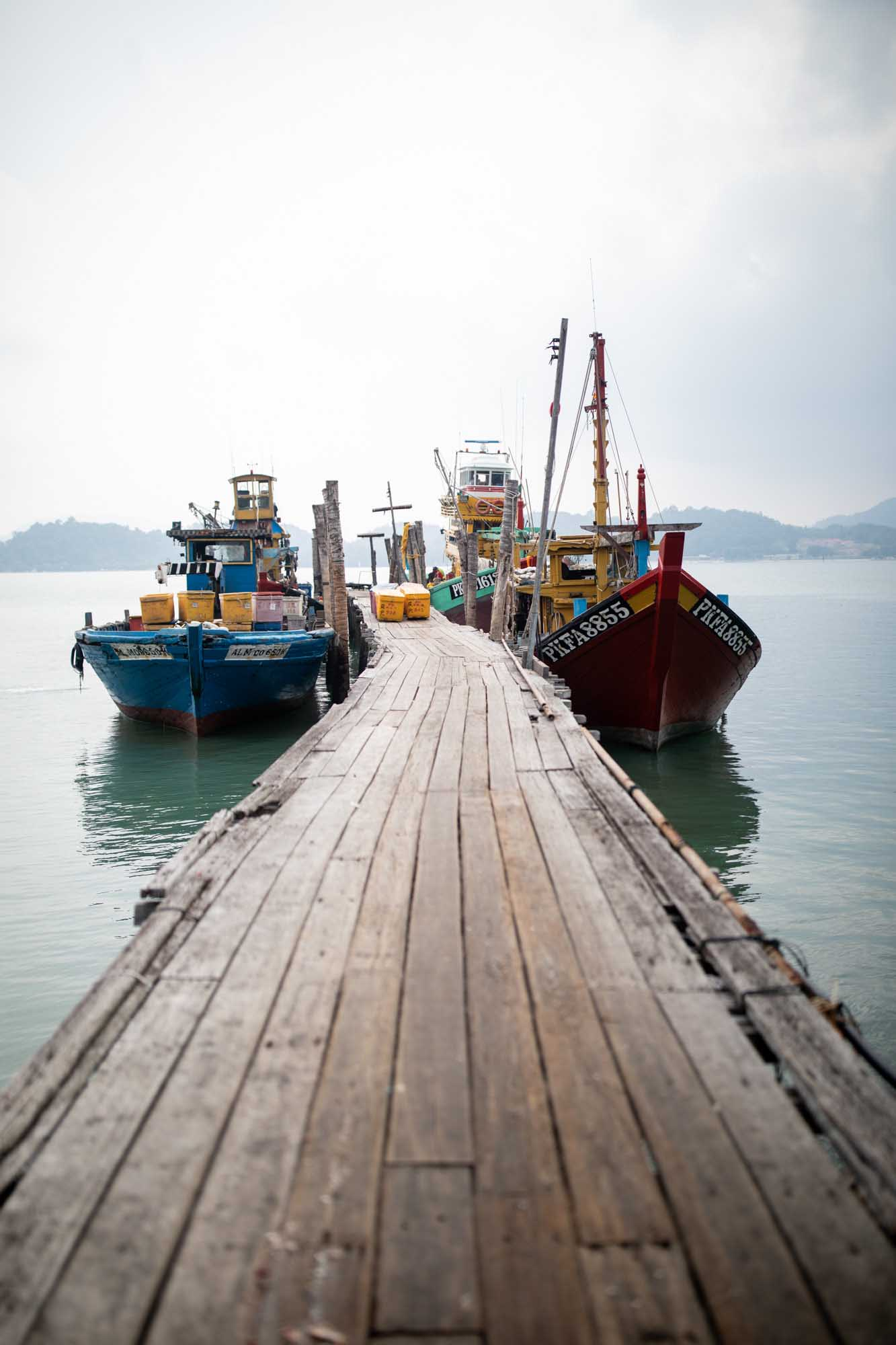 Fishing ships docked on wooden walkway in Pulau Pangkor, Malaysia. Travel Photography