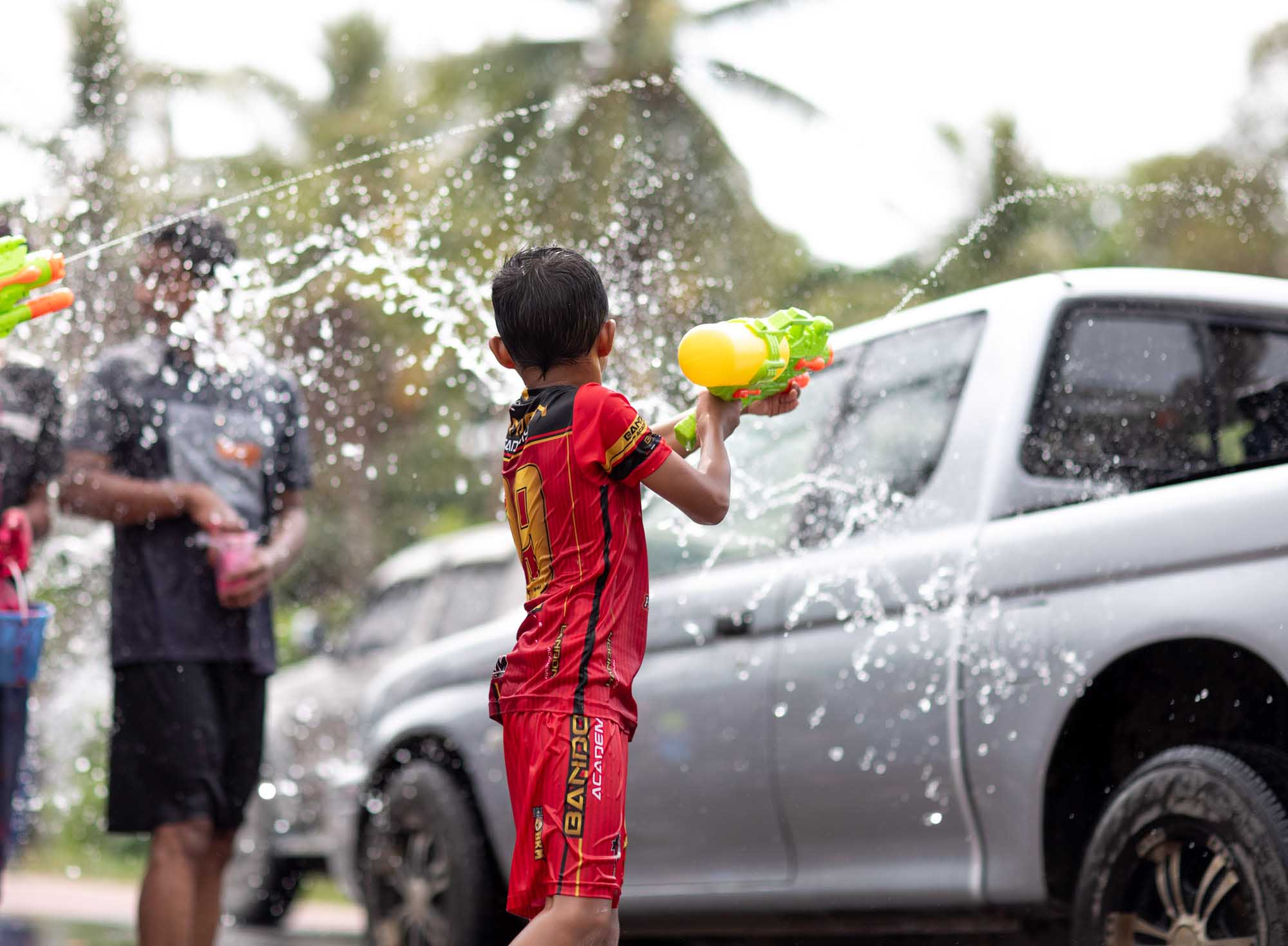 Boy shoots water gun at Songkran water festival in Phuket, Thailand | Travel Photography | Dramatic High Speed