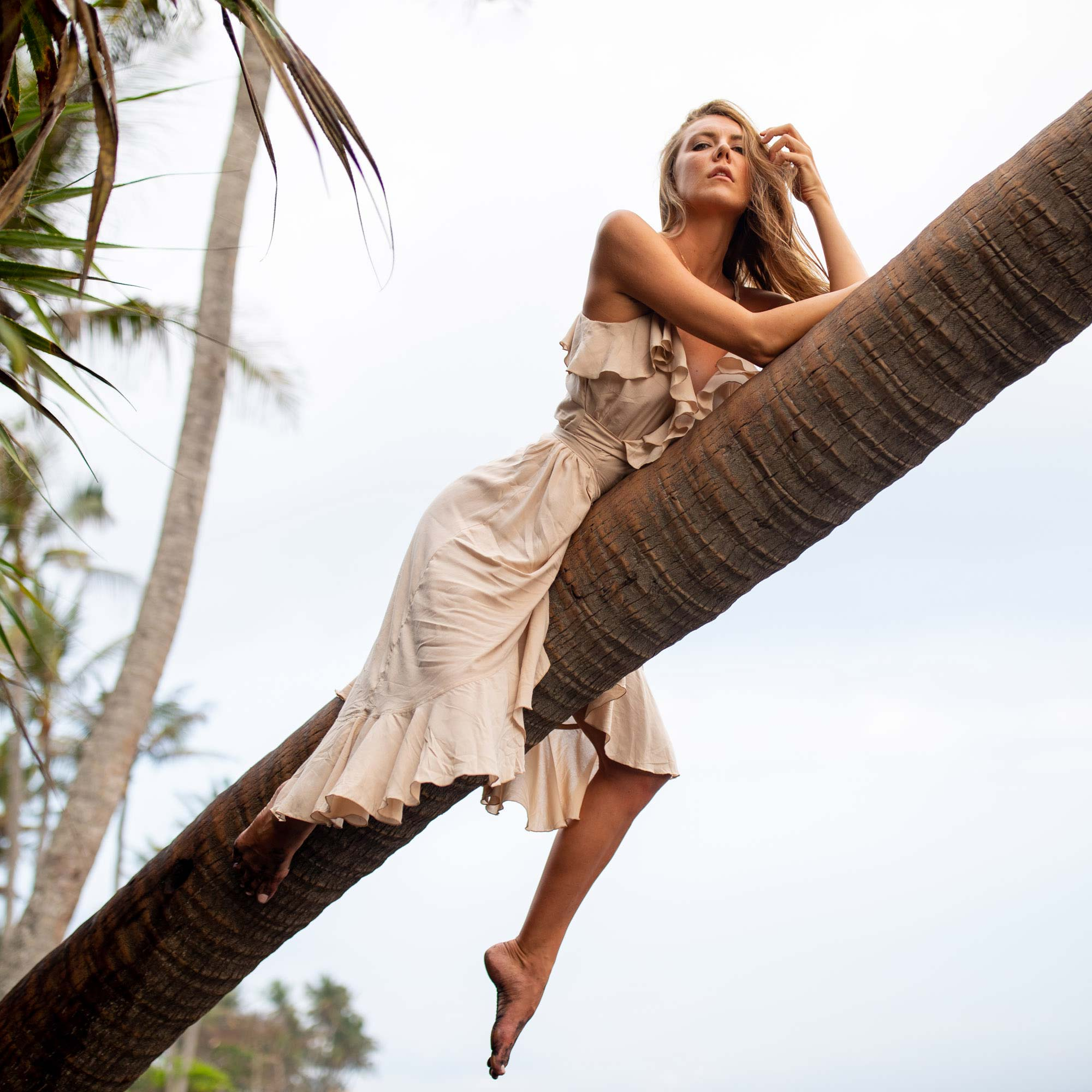 Woman climbs palm tree in flowing dress | Swimwear | Lifestyle Photography | Canggu, Bali, Indonesia