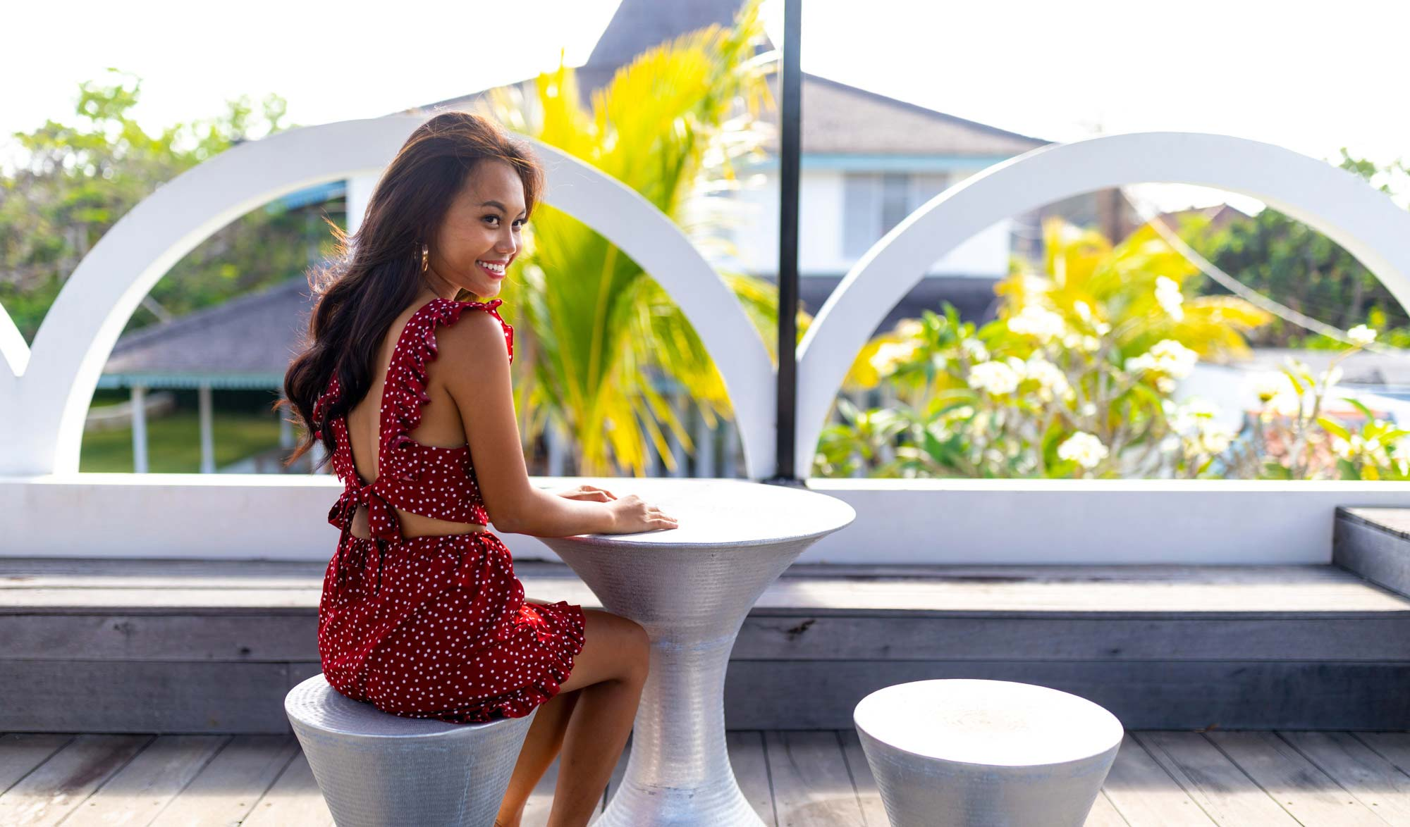 Woman sits at table at luxury villa in Bali wearing red | Lifestyle Photography | Swimwear Photography | Asian Bali Model | High Key Photography | Fashion Photography